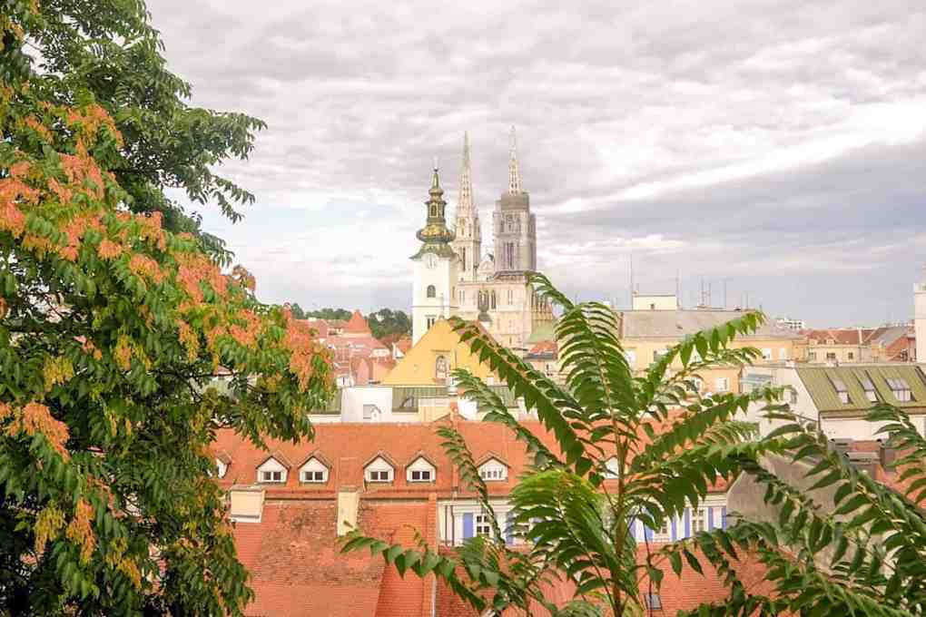 View of Zagreb roof tops with a church spire over the horizon, with tree branches in the foreground