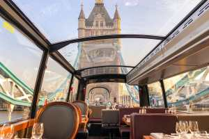 View of Tower Bridge from inside a glass roofed bus as it drives through the bridge. The Bus has tables set for dinner and it's a unique way to see London