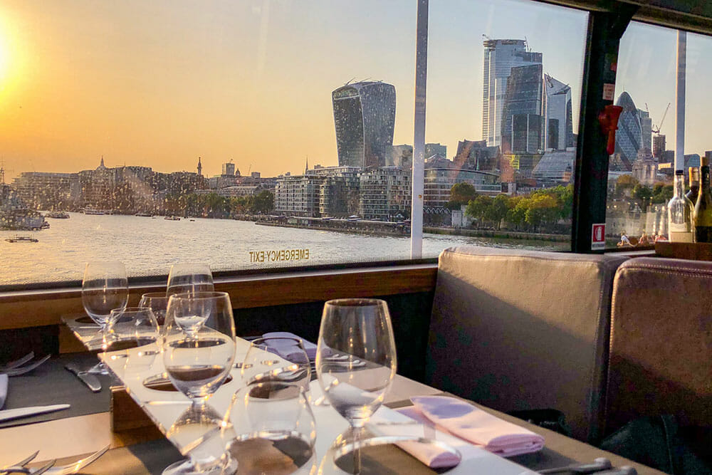Sunset view over The City of London from a table laid out for dinner inside a bus
