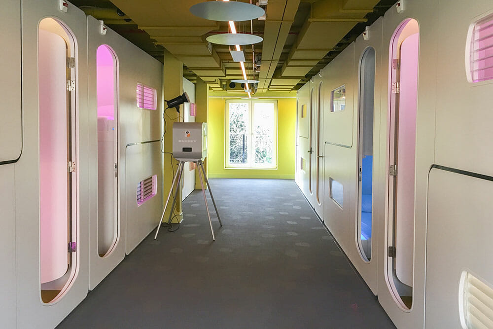 Corridor with spaceship like door lit up by bright pink and blue lights either side