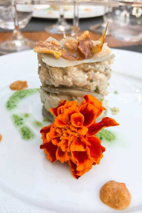 Crab and artichoke gateau stacked up with a flower on a plate