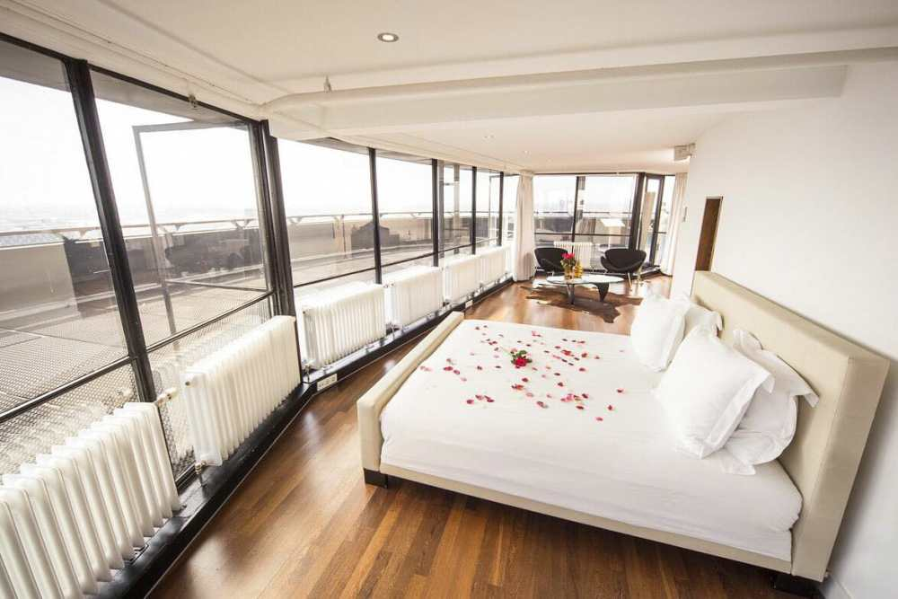 Room with a double bed with red rose petals on it and a wrap around floor to ceiling window. If you're wondering where to stay in Rotterdam for a special occasion, the Euromast is it.