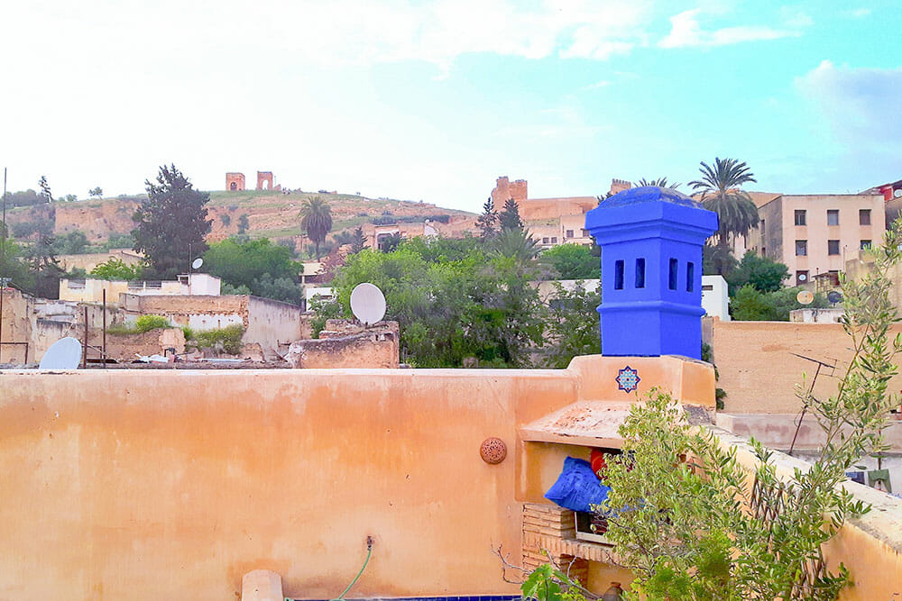 View of the hills from the roof terrace of the riad, with a blue chimney in the corner
