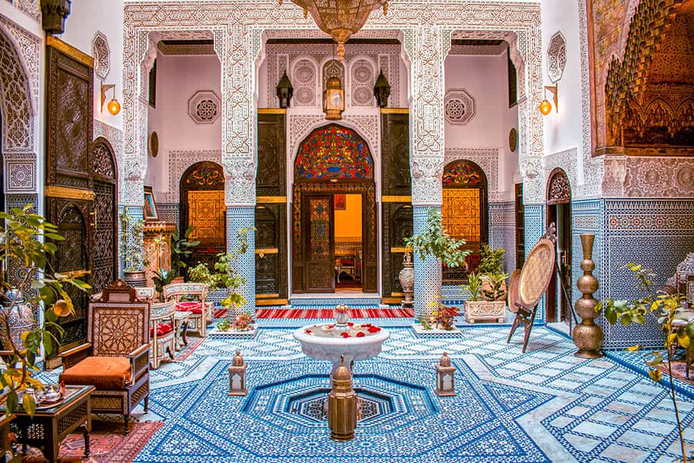 Intricately decorated courtyard with carved columns, blue and white tiles and a fountain in the middle. Riad Fes Maya is one of the best riads in Fes