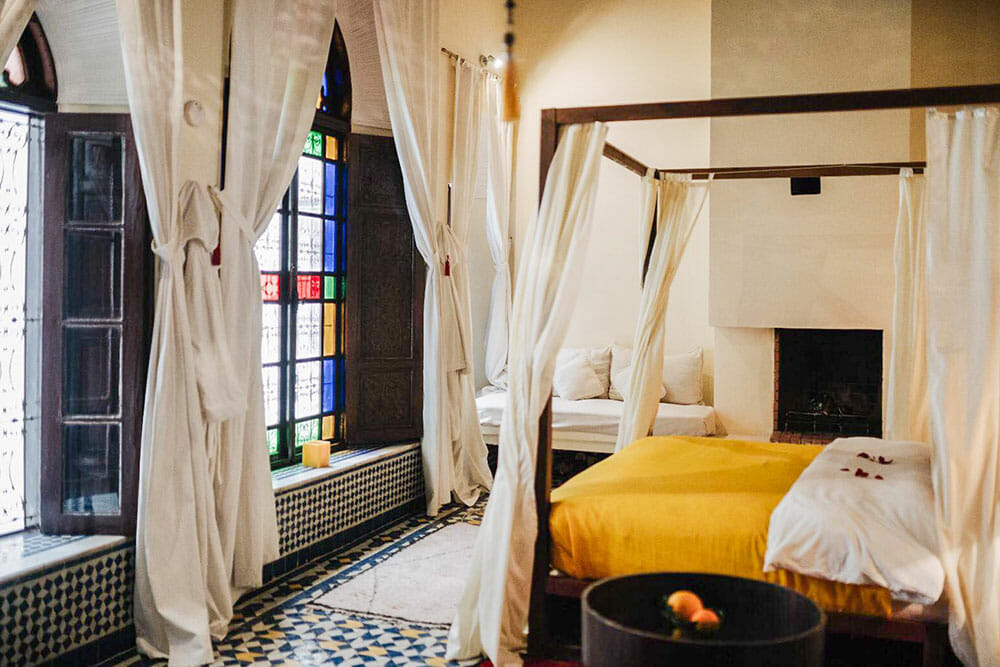 Room with four poster bed and yellow bedding with white curtains over the bed and the windows