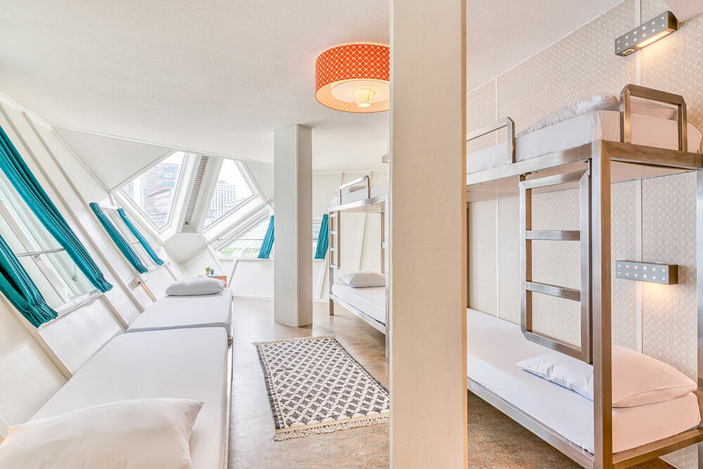 Room with two bunk beds with two columns in the middle of the room and walls at an angle - One of the most iconic places to stay in Rotterdam