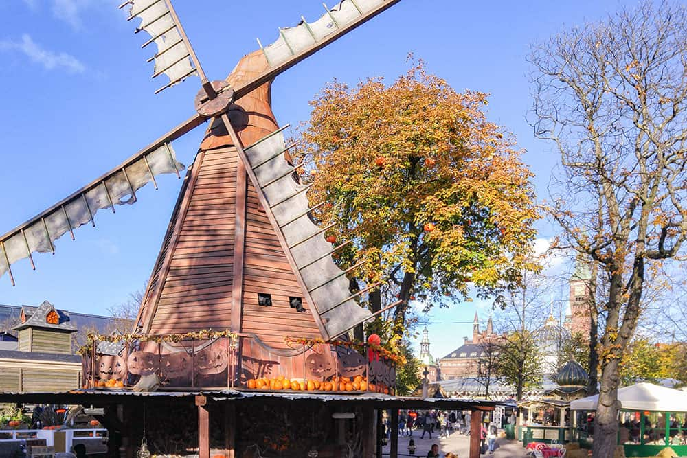 Windmill with worn out sails decorated with pumpkins all around it