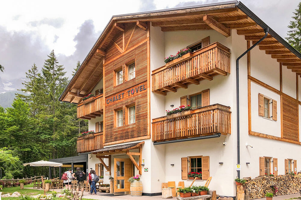 Alpine style three storey chalet with wooden balconies surrounded by trees