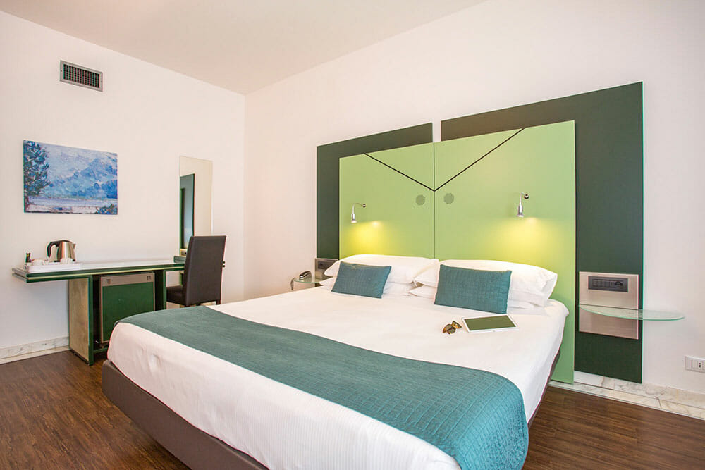 Room with large double bed with green cushions and headboard