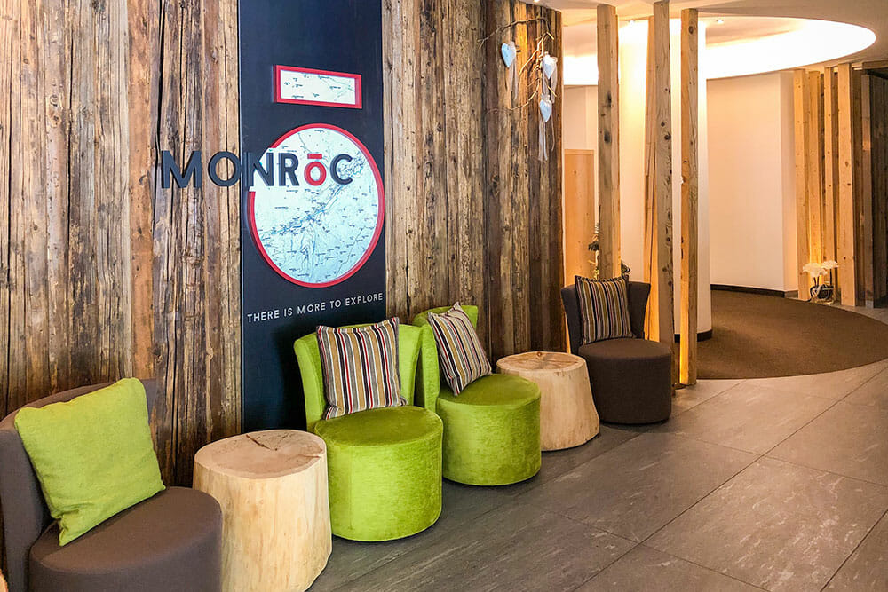 Green and brown chairs arranged with tree trunks and a wooden wall at Monroc, a lovely Trentino hotel