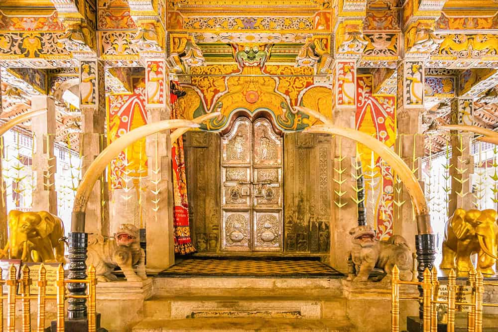 Interior of a temple with highly decorated walls with golden colours and patterns, and a gold door with two elephant tusks either side