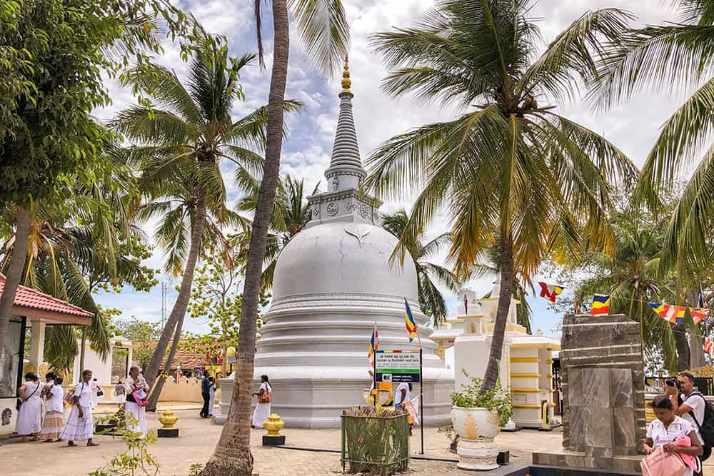 White pagoda surrounded by palm trees and people near it