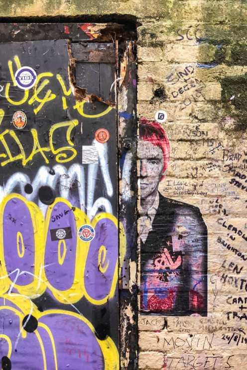 Wall with a black door in bad condition with graffiti all over it and a stencil of Paul Weller