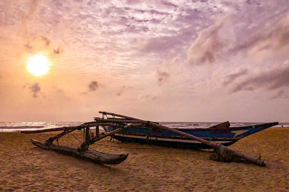 Fishing boat on the beach during sunset