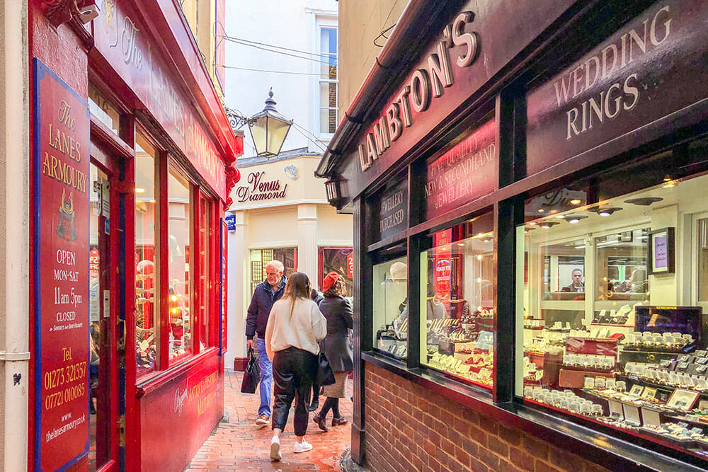 Narrow lane with a red shop on one side and a black jewellery shop on the other