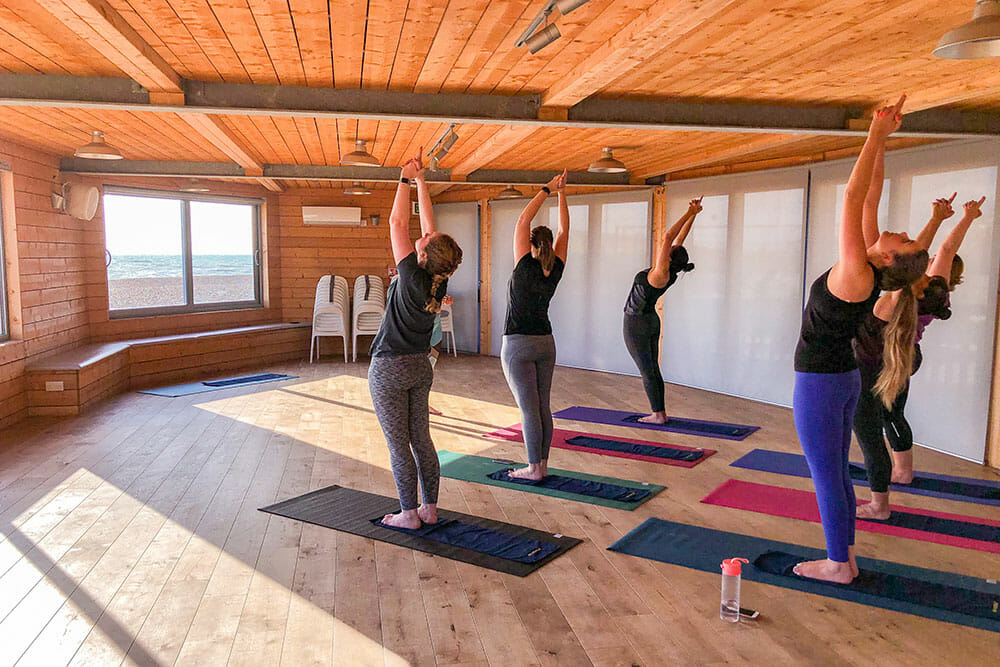 Six people practicing a stretching pose during a yoga class in a wooden space with beach and sea views