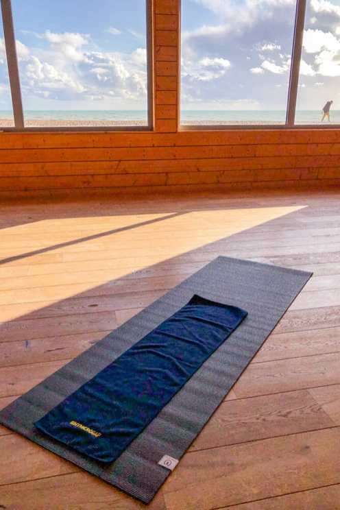 Yoga mat with towel positioned next to a window with sea views