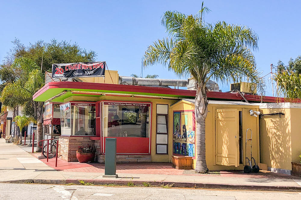 A green, red and yellow shack on a street corner with a palm tree outside