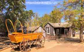 Old fashioned wagon cart and a small wooden house in Columbia. Visiting Columbia is one of the best things to do in Gold Country, California