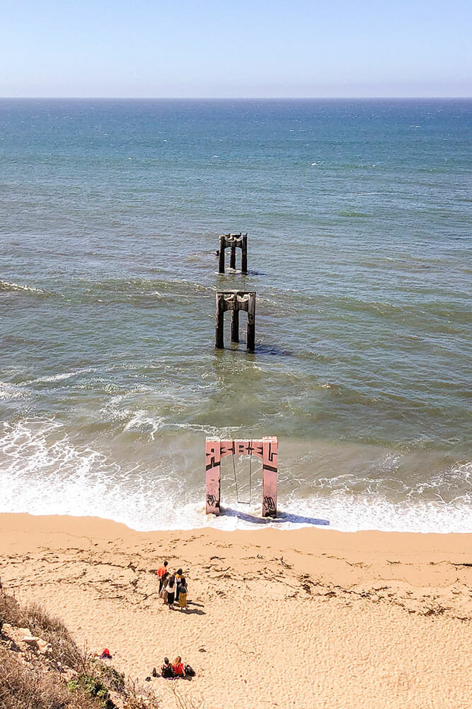 Three concrete pillar remains from an old pier going into the sea from a beach