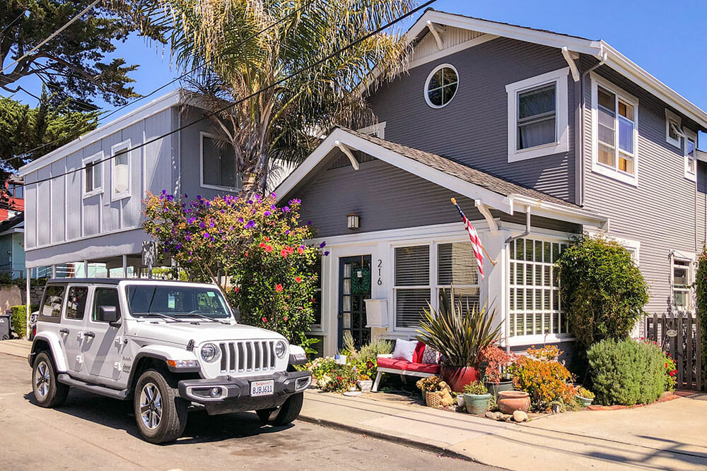 White jeep parked outside a grey wooden house, to make the most of your Santa Cruz day trip