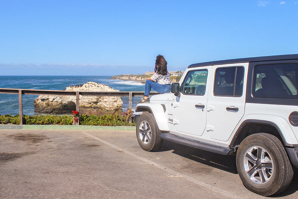 Woman sitting on the bonnet of a jeep looking out to sea