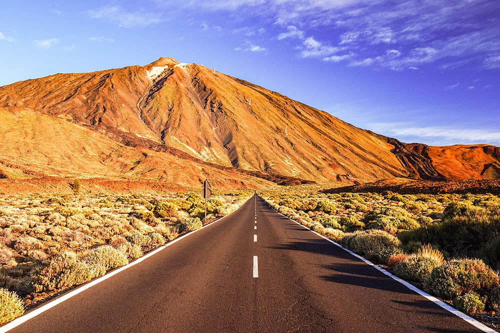 Road leading up to a volcano with an arid landscape around it, the perfect road for a road trip in Tenerife