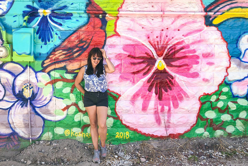 Woman standing in front of a colourful mural with hibiscus flowers and a red bird