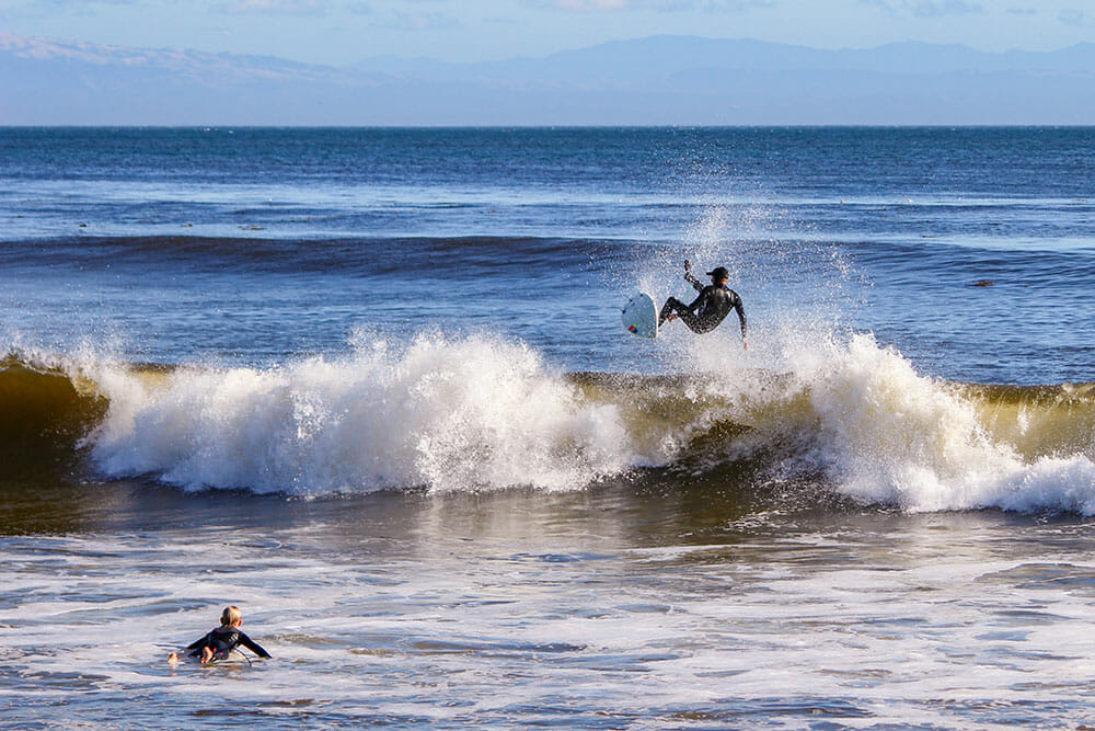 Two surfers in the sea, one jumping over a wave