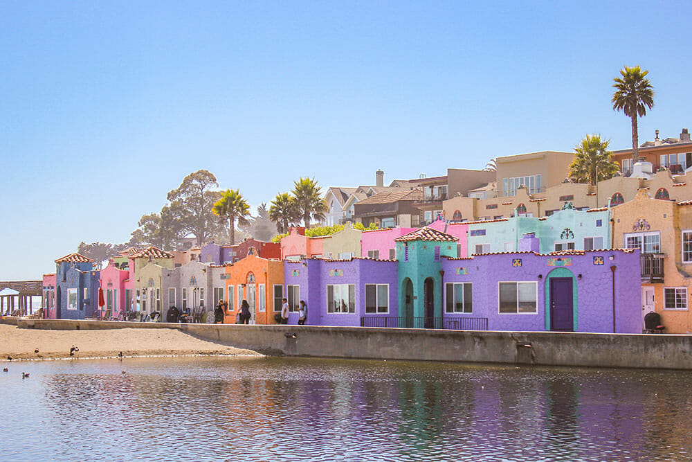 A group of brightly coloured houses lined up along the beach