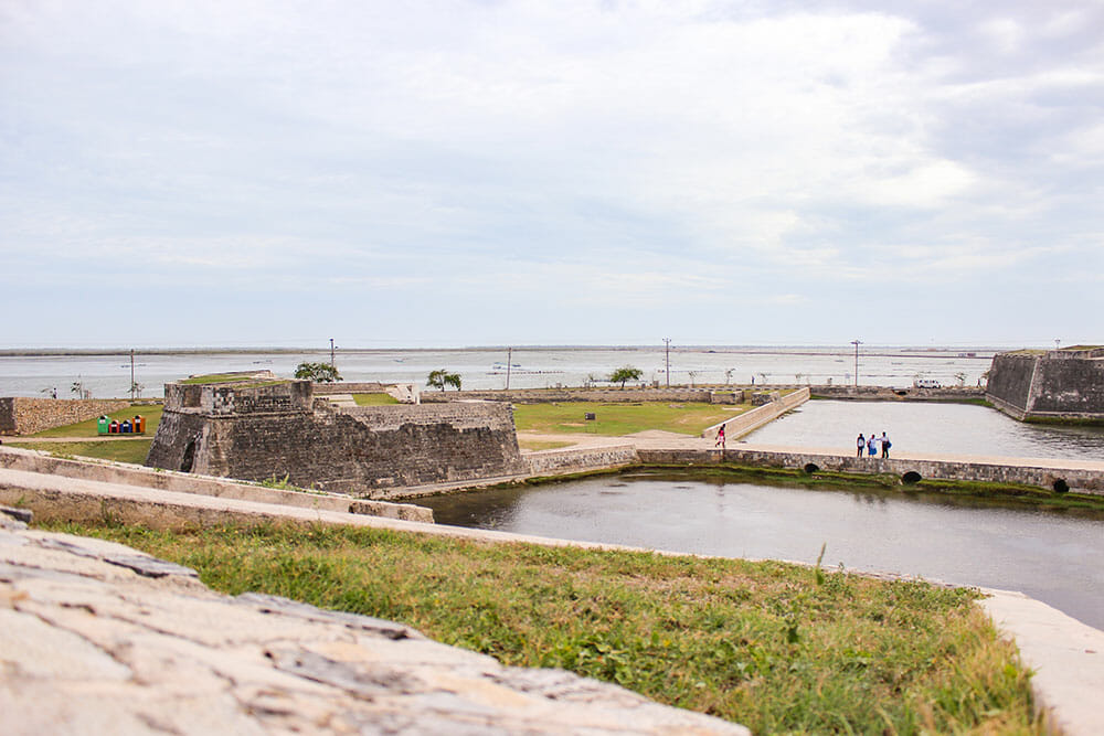 View over Jaffna Fort, moat and lagoon people walking around in the distance