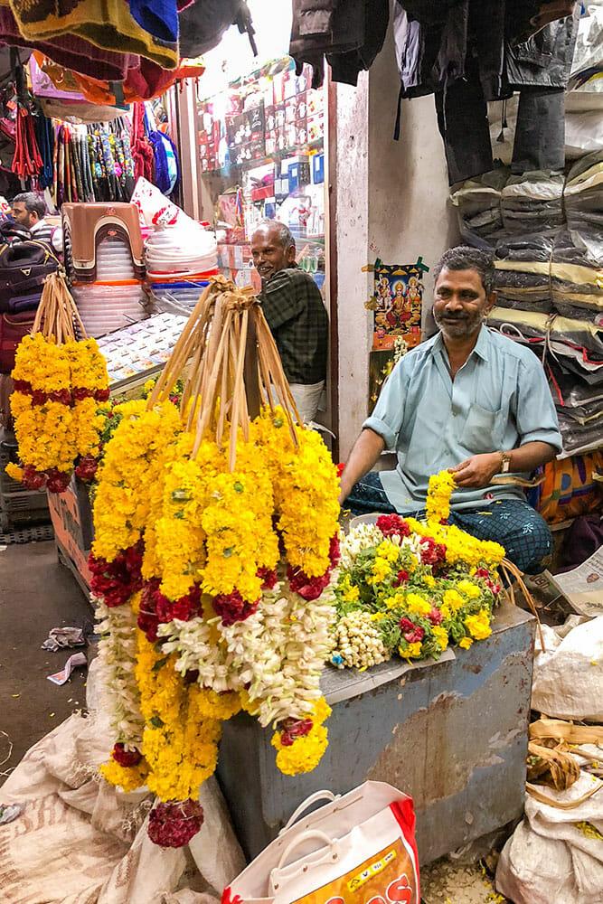 Man making flower garlands while sitting at flower garland stall in Munnar market