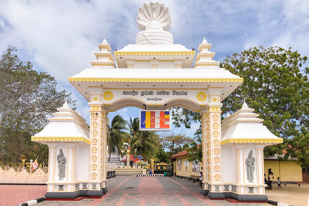 White gate with Sri Lankan writing and a Buddhist sign