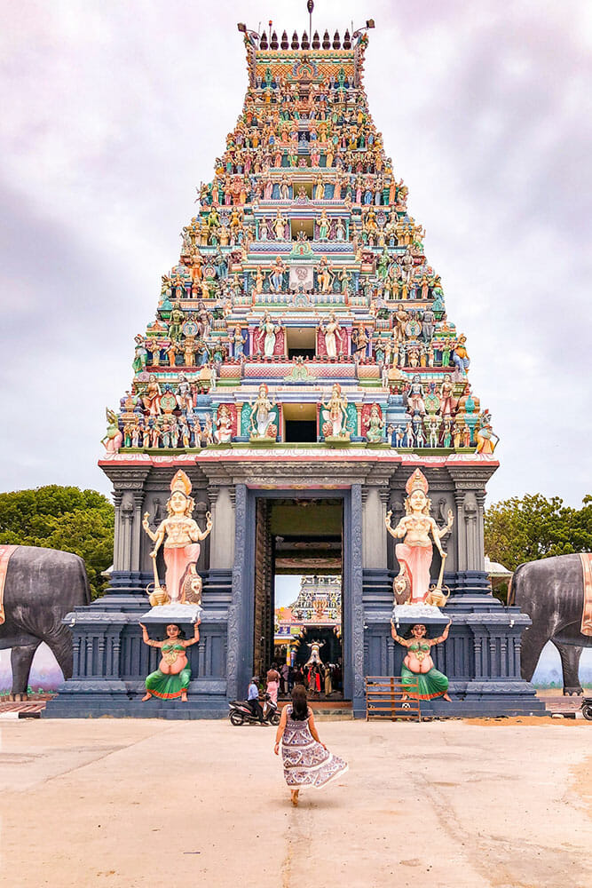Nagapooshani Amman Temple is one one of the tops places to visit in Jaffna. Here we see a woman walking towards the tall Hindu gate tower decorated in blue and green colours