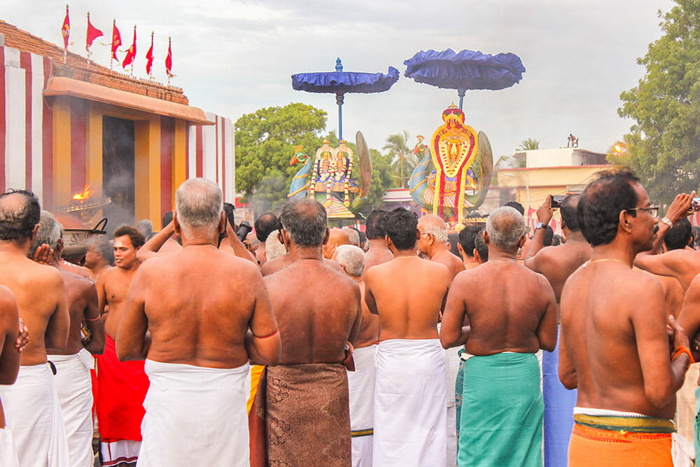Large group of Hindu men dressed with sarongs and no tops looking away at religious symbols approaching under umbrellas