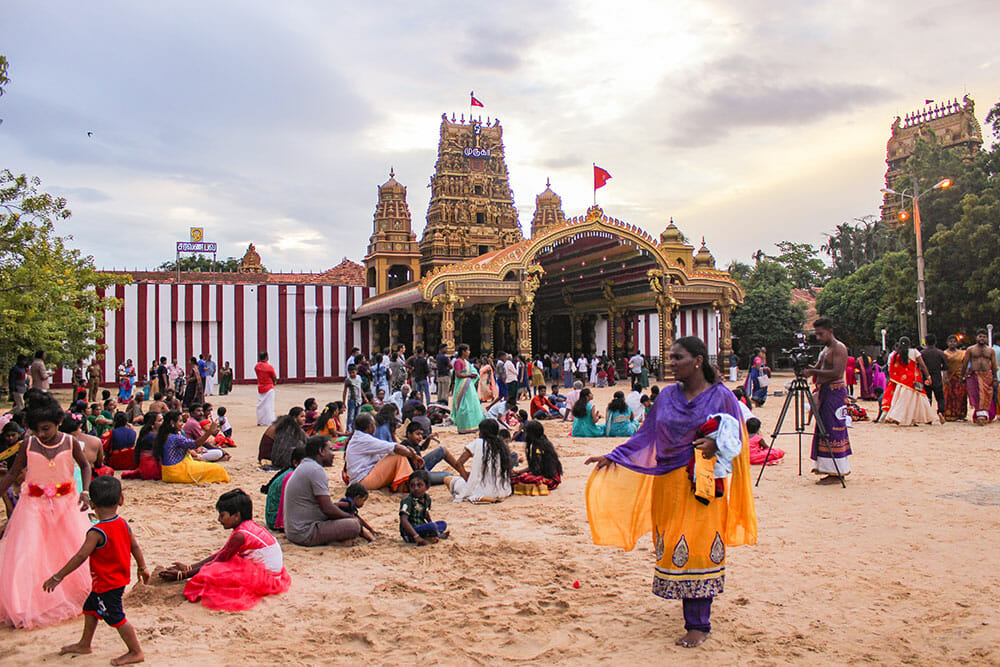 A large group of people walking and sitting on the sand outside a golden Hindu temple gate