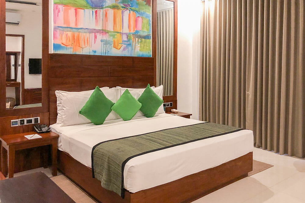 Hotel room with large double bed with white bed linen and three green cushions. There is a colourful painting above the headboard