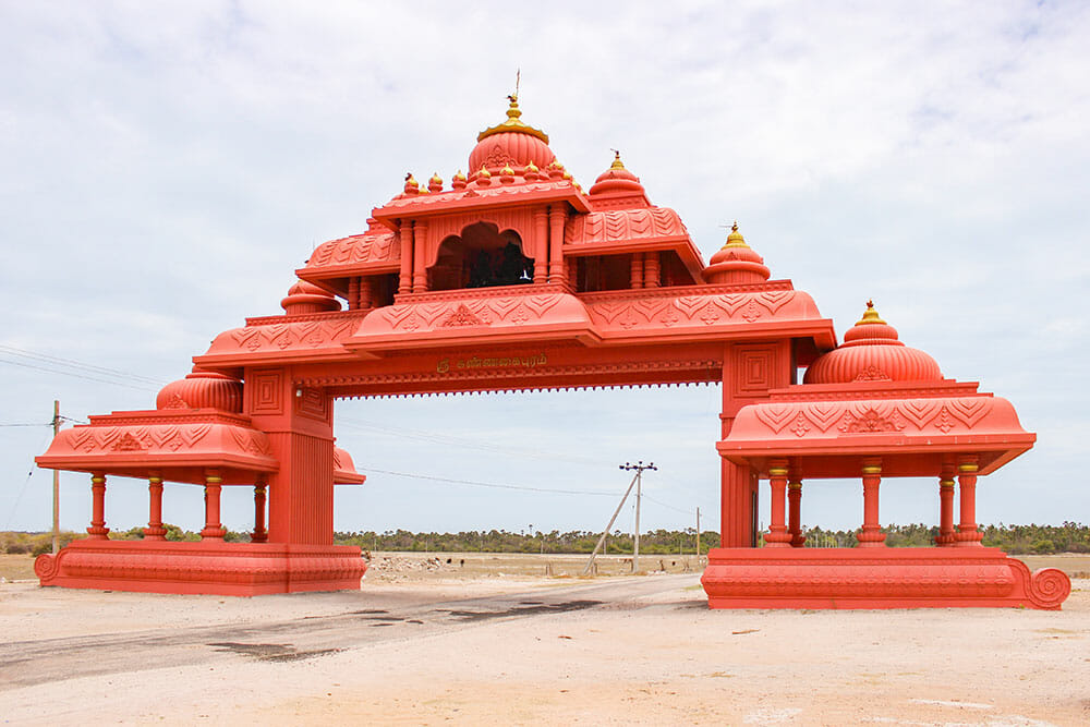 Large red Hindu gate with seven domes and columns at either side, over a dirt track with nothing around it