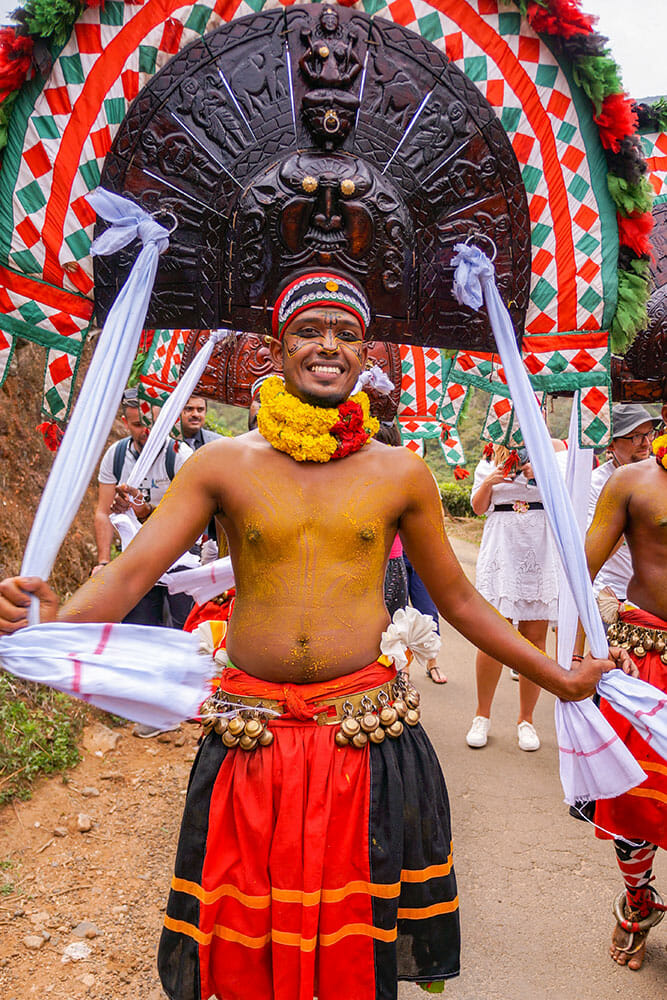Traditional Kerala male dancer wearing a red and black skirt with bells on his hips and a heavy wooden head dress that he keeps in place by holding two long white ribbons