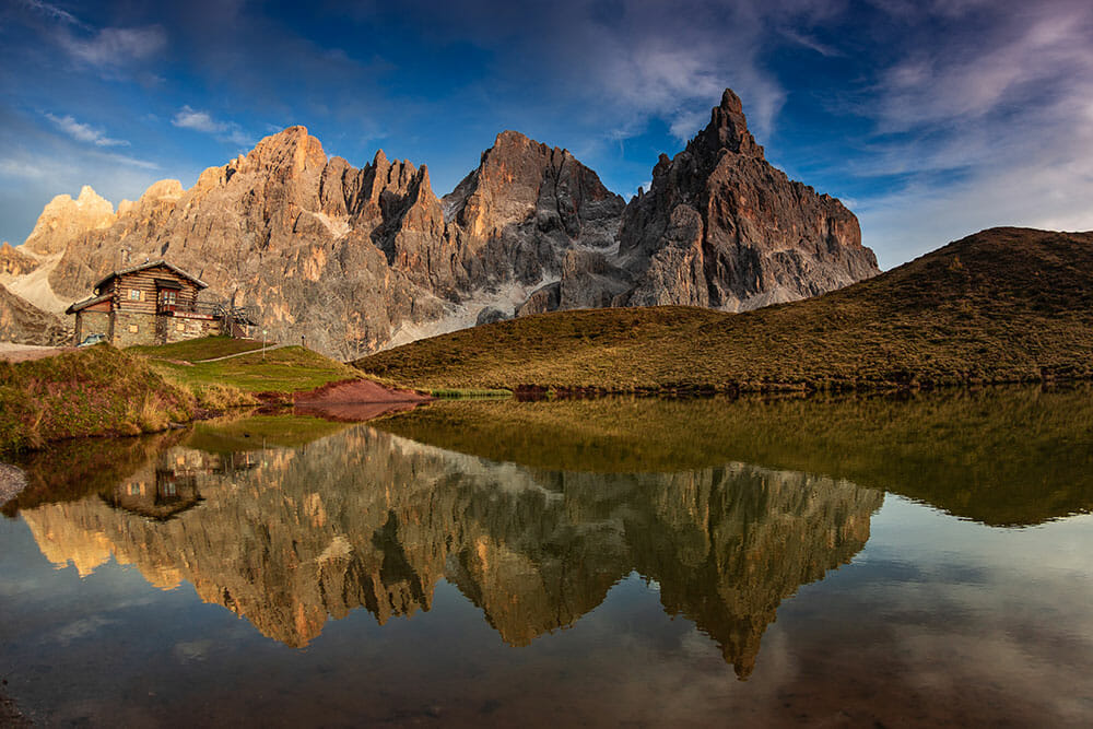 Reflection on a lake of the jagged mountains and a mountain refuge