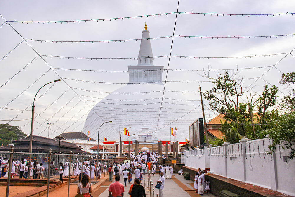 People dressed in white walking towards a large white stupa