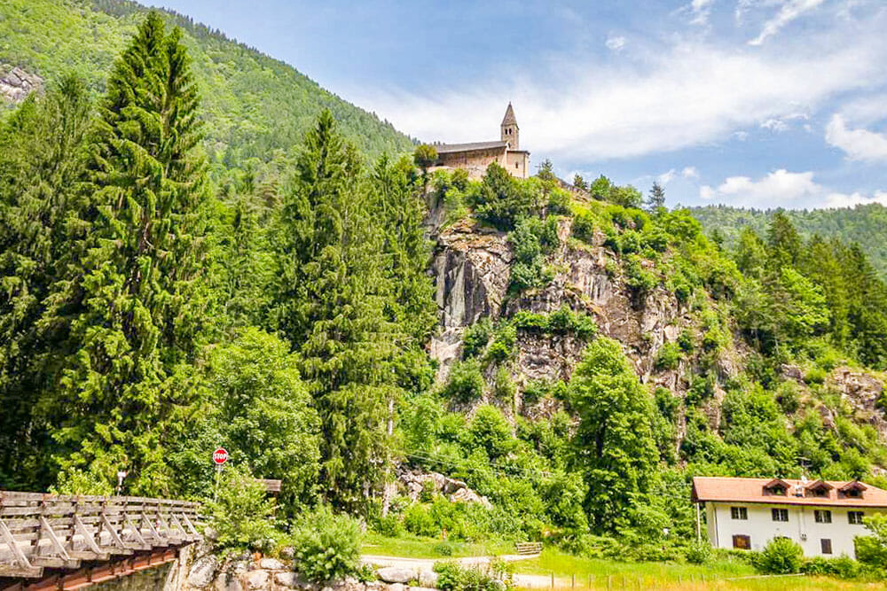 Church on top of a rocky outcrop on a mountain covered with green alpine trees
