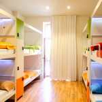 Room with eight colourful bunk beds with lockers and a white curtain over a tall window