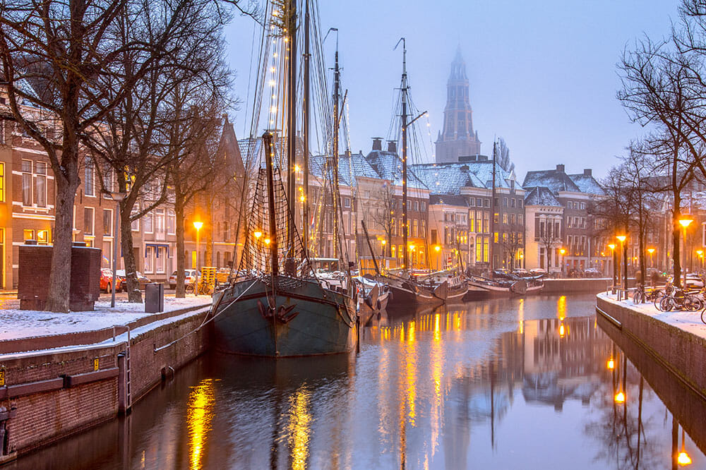 Canal with ships with houses and church tower in the background covered in snow