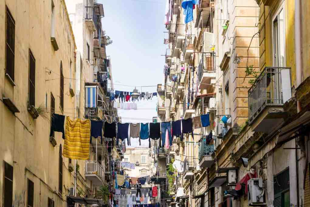 Street view of old town in Naples with laundry hanging out of windows. The historic centre is the starting point when spending one day in Naples