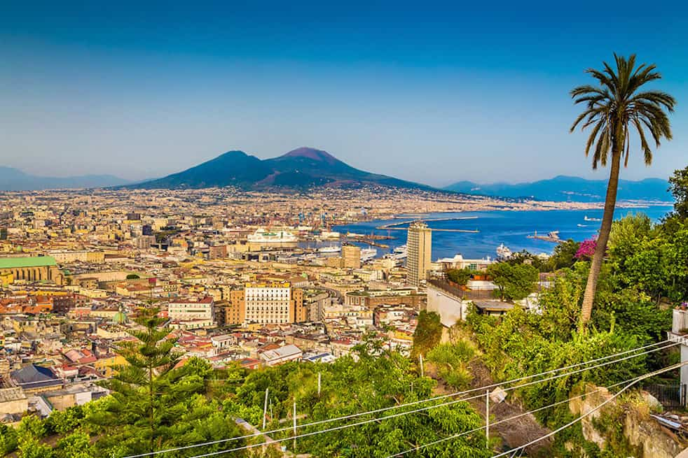 Scenic picture-postcard view of the city of Napoli (Naples) with famous Mount Vesuvius in the background in golden evening light at sunset, Campania, Italy. The best view when spending one day in Naples