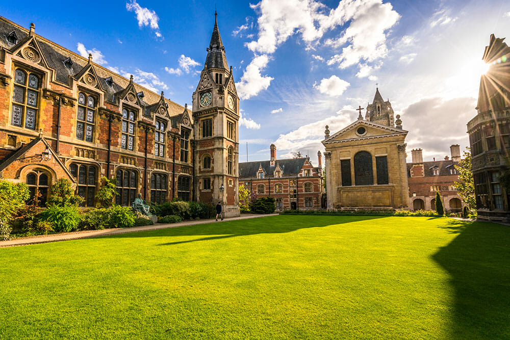 Cambridge University buildings with clock tower and green