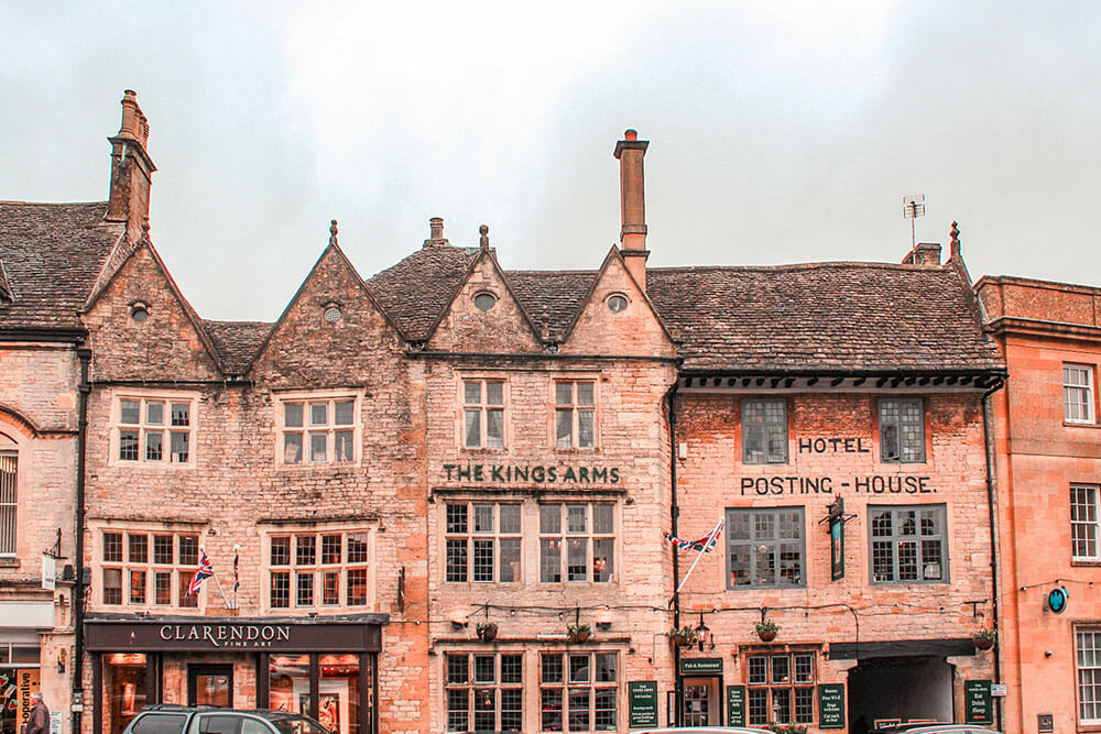 Old red brick three storey houses with signs reading The Kings Arms and Hotel Posting House