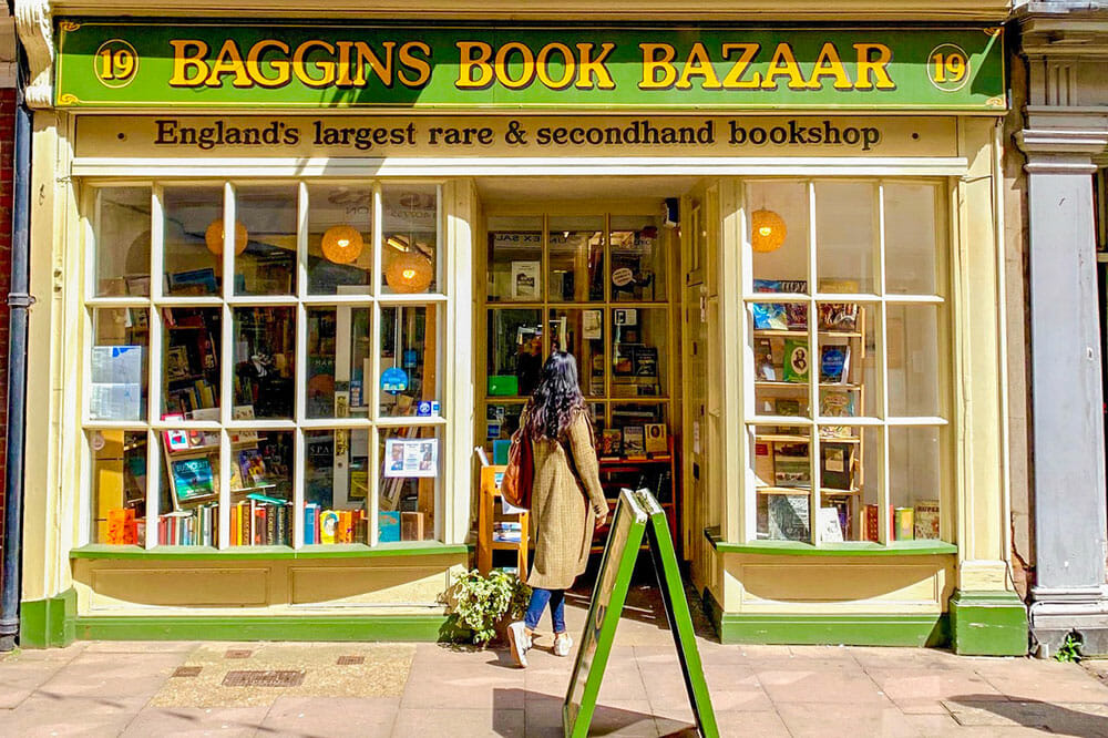 Standing outside a yellow and green fronted bookshop