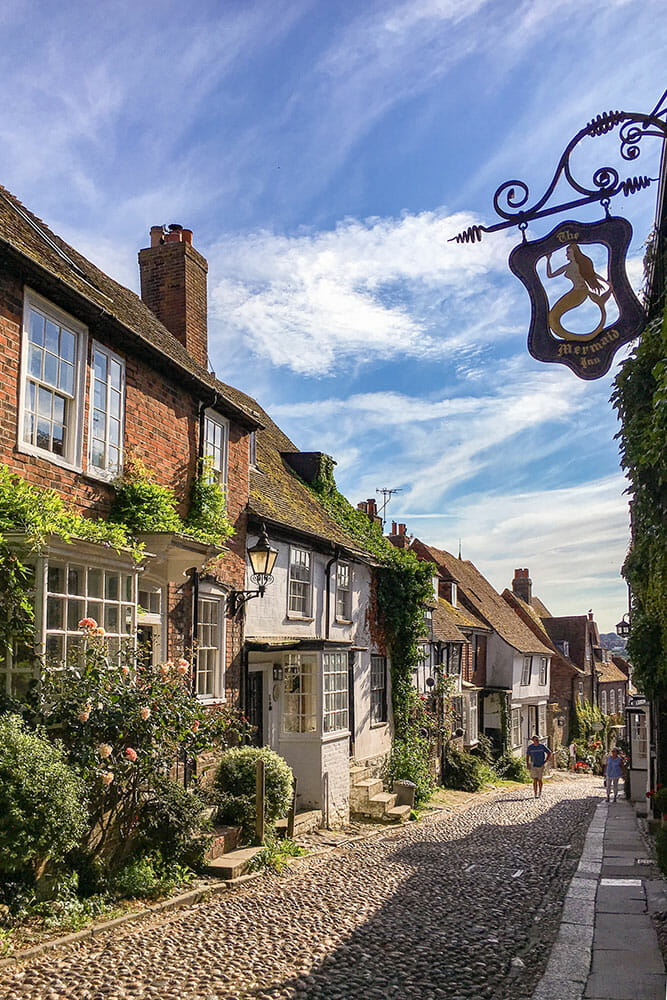 Cobbled narrow street lined with small higgledy-piggledy cottages